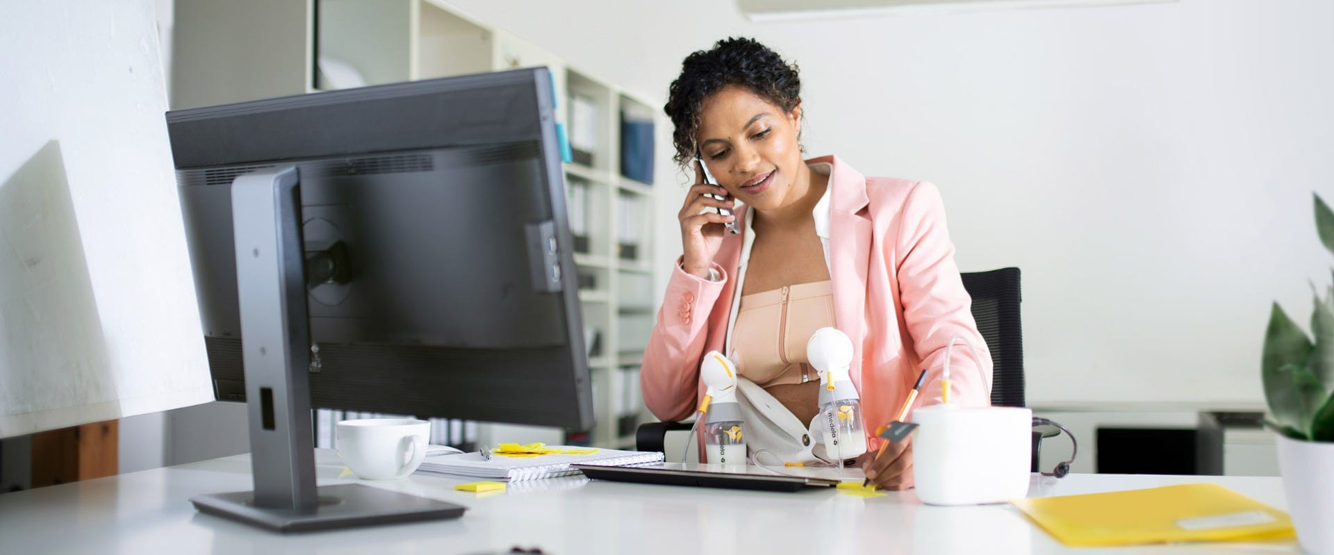 Woman cleaning breast pump shield in front of her laptop